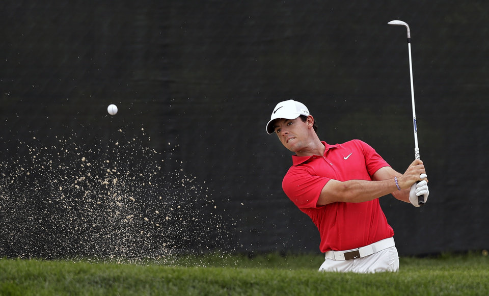 Photo - Rory McIlroy, of Northern Ireland, hits from a bunker on the 13th hole during the first round of play at The Barclays golf tournament Thursday, Aug. 21, 2014, in Paramus, N.J.  (AP Photo/Mel Evans)