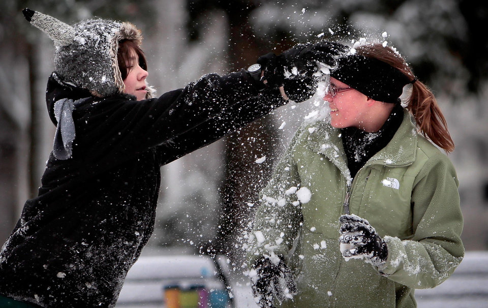 Photo - Ian Rone, 12, surprises Alena Byrn. 16, with a face full of flakes while snowball fighting at the Overton Shell, Wednesday Dec. 26, 2012 in Memphis, Tenn. Memphis managed to avoid the heavy snow that blanketed much of Arkansas, but Overton park was bustling with kids taking advantage of an almost white Christmas. (AP Photo/The Commercial Appeal, Jim Weber)