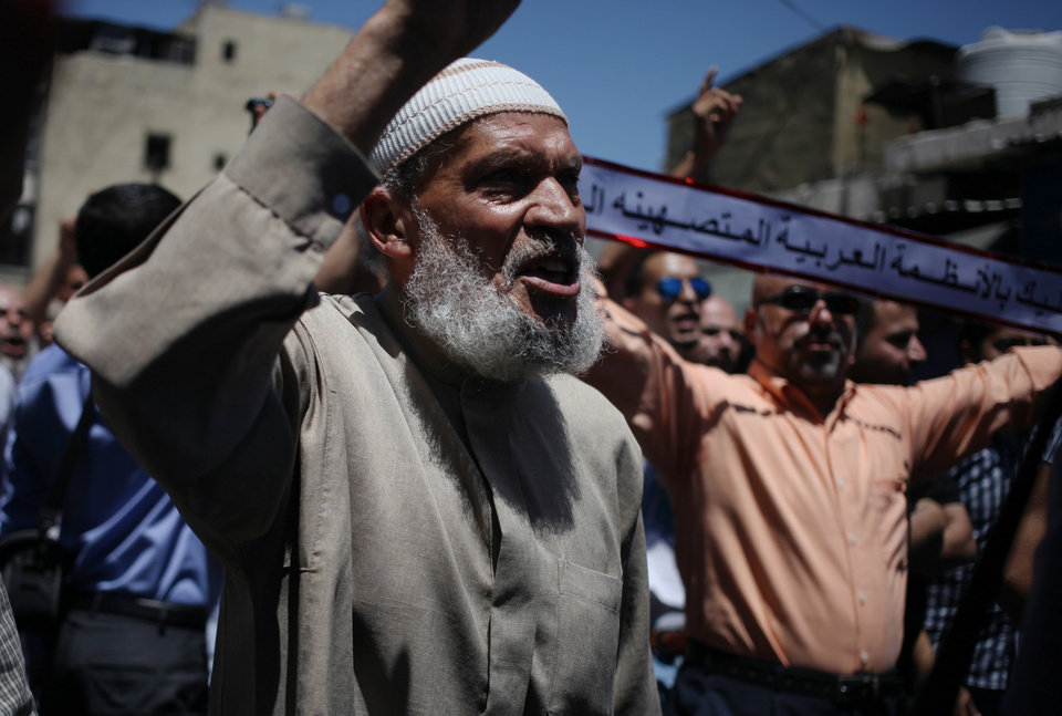 Photo - Protesters chant slogans against Israel to condemn its bombing on Gaza and to demand Hamas and other Palestinian brigades in Gaza reject any truce with Israel, during a protest by followers of the Muslim Brotherhood in Amman, Jordan, Friday, July 18, 2014. The Arabic writing reads,