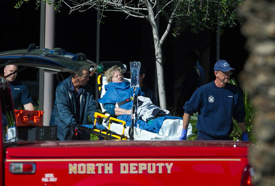 Photo - A woman is taken to a paramedic truck from an office building where a shooter opened fire in north central Phoenix on Wednesday, Jan. 30, 2013. (AP Photo/The Arizona Republic, Michael Schennum)