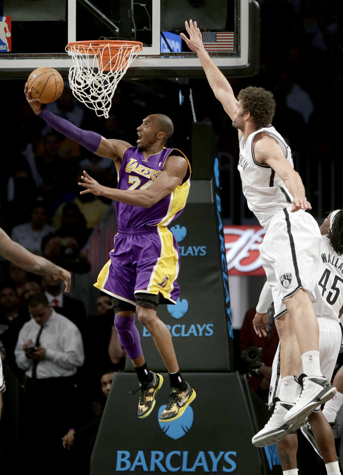 Los Angeles Lakers' Kobe Bryant, left, puts up a shot underneath the basket while Brooklyn Nets' Brook Lopez defends during the first half of the NBA basketball game at the Barclays Center Tuesday, Feb. 5, 2013 in New York. (AP Photo/Seth Wenig)