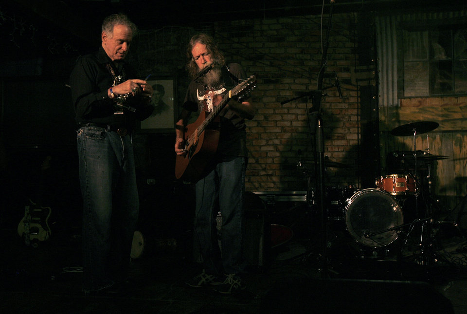 Photo -  Randy Crouch, right, tunes his guitar with fellow flute player and bandmate at his side at the Brick Street Cafe during Woody Fest in Okemah, Okla.  Photo by Ashley McKee, The Oklahoman