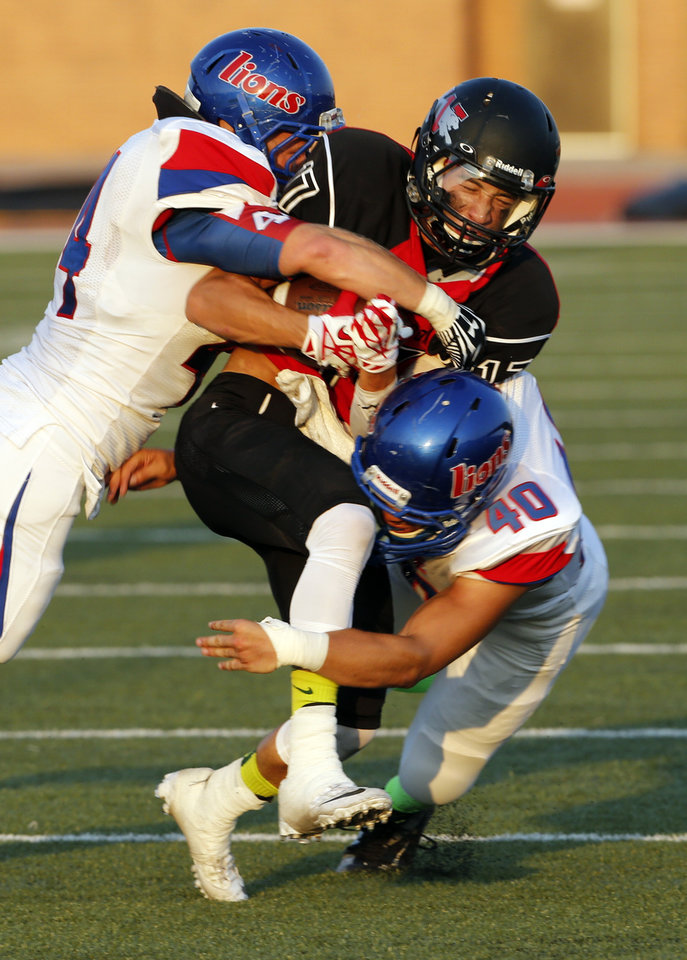 Photo - Jaguare's Jake Dyer is brought down by Jordan Norris (4) and Larry Briggs (40) as Westmoore plays Moore High School on Friday, Sept. 6, 2013 in Moore, Okla.  Photo by Steve Sisney, The Oklahoman