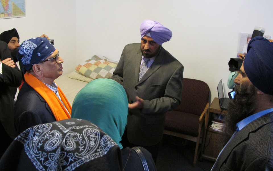 Indian External Affairs Minister S.M. Krishna, left, in orange saropa, listens Thursday, Oct. 14, 2012, as Sikh Temple of Wisconsin Trustee Harcharan Gill, center, in turban, describes how Michael Wade Page stormed into the temple in suburban Milwaukee on Aug. 5 and opened fire, killing six worshippers. (AP Photo/Todd Richmond)