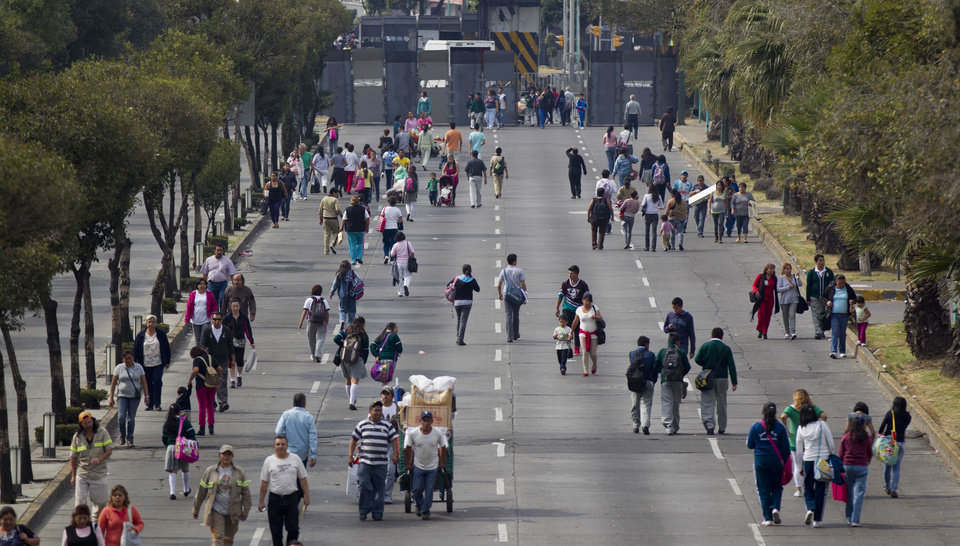 Photo -   People walk at the barricaded street where Mexico's Congress is located in Mexico City, Monday, Nov. 26, 2012. Police heightened security around the building where Mexico's President-elect Enrique Pena Nieto, of the Institutional Revolutionary Party (PRI) will be sworn-in on Dec. 1. (AP Photo/Eduardo Verdugo)