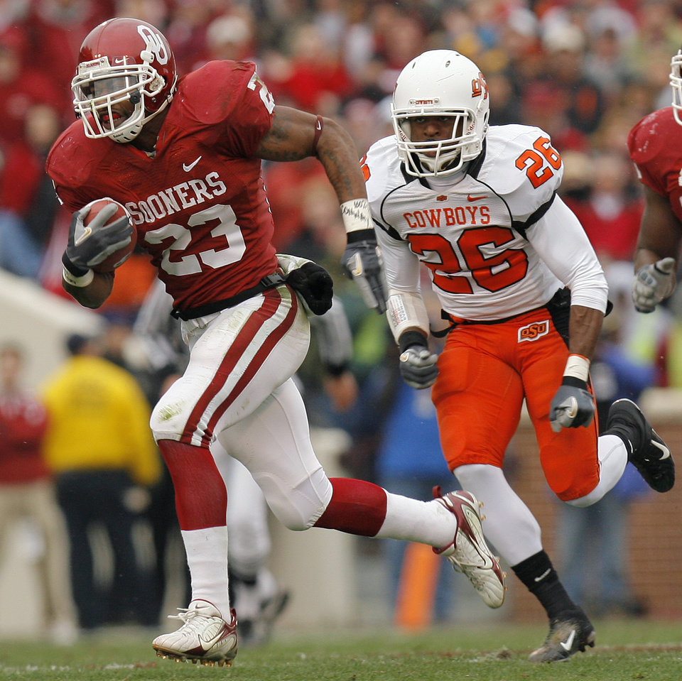 Photo - Oklahoma's Allen Patrick (23) takes the ball up field past Oklahoma State's Quinton Moore (26) during the first half of the college football game between the University of Oklahoma Sooners (OU) and the Oklahoma State University Cowboys (OSU) at the Gaylord Family-Memorial Stadium on Saturday, Nov. 24, 2007, in Norman, Okla. 
