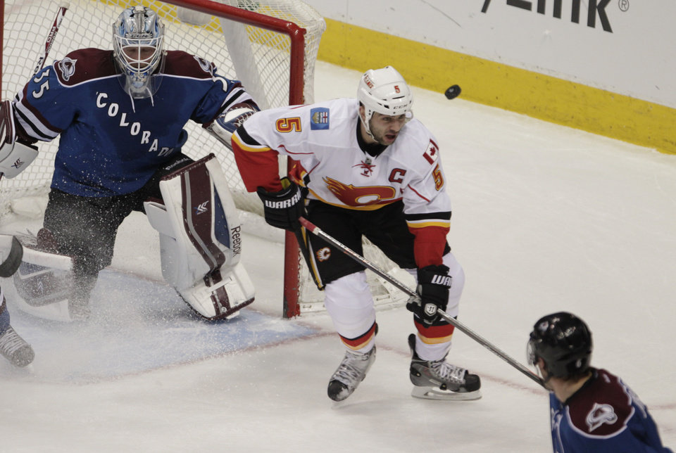 Photo - The puck bounces past Calgary Flames defenseman Mark Giordano (5) as Colorado Avalanche goalie Jean-Sebastien Giguere (35) defends the goal in the first period of an NHL game in Denver on Monday, Jan. 6, 2014. (AP Photo/Joe Mahoney)