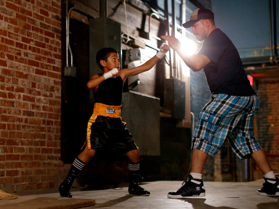 Photo -  Chris Barba, 9, of Edmond, warms up with family friend Jose Barrientos before his first fight at The Underground Arena in Oklahoma City, Saturday, June 15, 2013. Chris