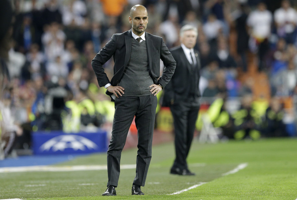 Photo - Bayern head coach Pep Guardiola, left, watches the Champions League semifinal first leg soccer match between Real Madrid and Bayern Munich at the Santiago Bernabeu stadium in Madrid, Spain, Wednesday, April 23, 2014. (AP Photo/Paul White)