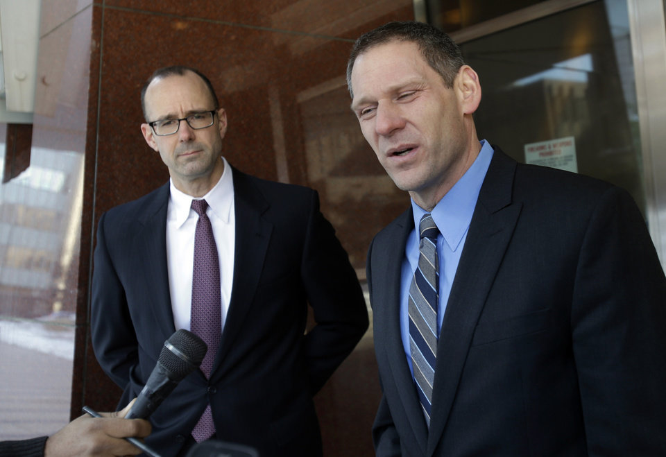 Prosecutor Andrew Winter, left, listens as fellow prosecutor Steve Schleicher talks to reporters after a federal jury Tuesday, March 19, 2013, in Minneapolis convicted three alleged members of an American Indian gang accused of terrorizing people in the Upper Midwest. (AP Photo/Jim Mone)