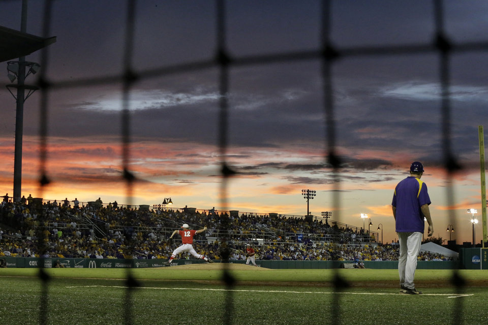 Photo - Houston pitcher Jared Robinson (12) pitches as the sun sets in the third inning of an NCAA college baseball regional tournament game against LSU in Baton Rouge, La., Monday, June 2, 2014. (AP Photo/Gerald Herbert)
