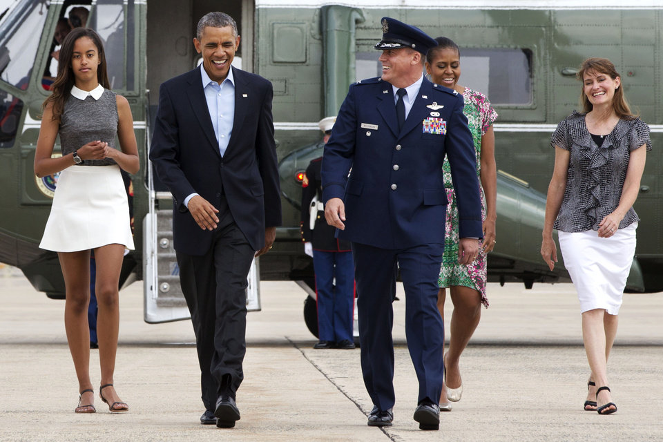 Photo - FILE - In this Aug. 9, 2014, file photo, President Barack Obama second from left, walks from Marine One with Vice Commander of the 89th Airlift Wing at Andrew Air Force Base Col. Preston Williamson IV, third from left, followed by his  daughter Malia Obama, left, first lady Michelle Obama, second from right and Christine Williamson, to board Air Force One at Andrews Air Force Base, Md., en route to a family vacation on the Massachusetts island of Martha's Vineyard. Obama arrived on the Massachusetts island of Martha's Vineyard with one daughter, and the other daughter may be at his side when his two-week getaway ends later this month. In a first for Obama family summer vacations, neither teenager is spending the entire time with her father. (AP Photo/Jacquelyn Martin, File)