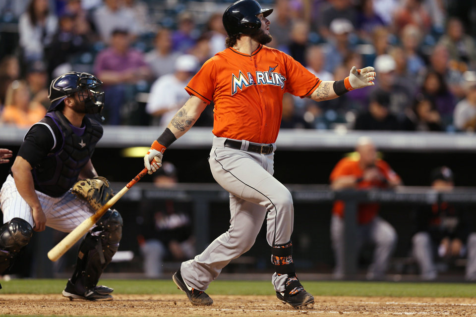 Photo - Miami Marlins' Jarrod Saltalamacchia watches his RBI double in front of Colorado Rockies catcher Micahel McKenry in the fifth inning of a baseball game in Denver on Saturday, Aug. 23, 2014. (AP Photo/David Zalubowski)