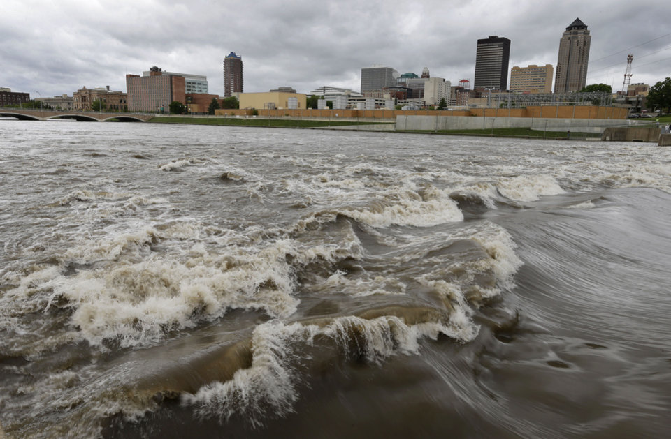 """Photo - FILE - In this May 30, 2013, file photo, water splashes over the Center Street Dam in the swollen Des Moines River in downtown Des Moines, Iowa.  Climate change's assorted harms """"are expected to become increasingly disruptive across the nation throughout this century and beyond,"""" the National Climate Assessment concluded Tuesday. (AP Photo/Charlie Neibergall, File)"""