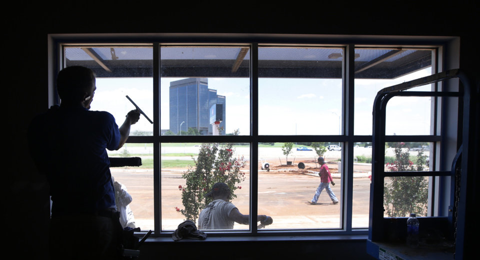Photo -  Seth Williams cleans a window at LifeChurch.tv at Broadway Extension and Britton Road in Oklahoma City. Photo By Steve Gooch, The Oklahoman   Steve Gooch - The Oklahoman