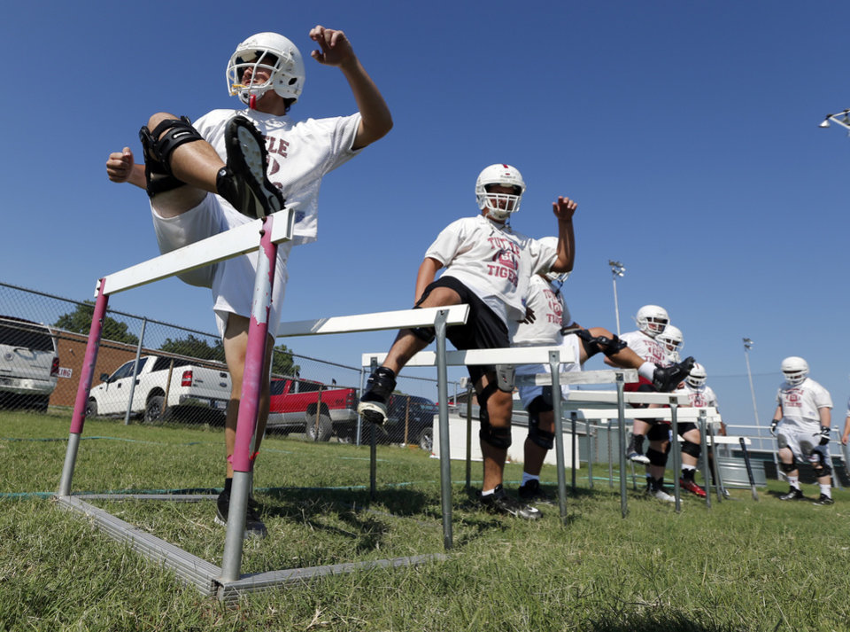 Photo - Teague Fox and teammates go through stretching drills during high school football practice on Tuesday, Aug. 12, 2014 in Tuttle, Okla. Photo by Steve Sisney, The Oklahoman