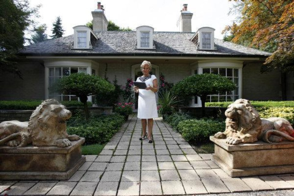 Photo - In this Aug. 23, 2011 photo, real estate agent Ronni Keating waits outside for a client to view a home in Bloomfield Hills, Mich. (AP Photo/Paul Sancya) ORG XMIT: MIPS203