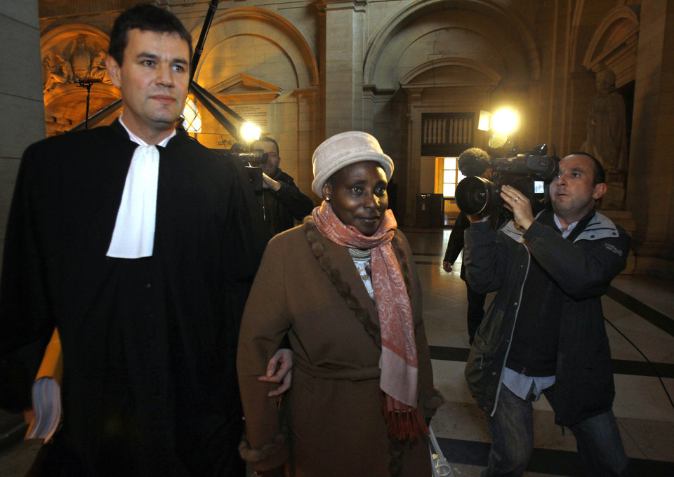 Photo -   Agathe Habyarimana, center, the widow of former President of Rwanda Juvenal Habyarimana, arrives with her lawyer Philippe Meillac, left, at Paris court house, Tuesday, Jan. 10, 2012. A French investigator is releasing the results of his investigation Tuesday into the downing of the plane of President Juvenal Habyarimana, which helped spark Rwanda's 1994 genocide. (AP Photo/Remy de la Mauviniere)