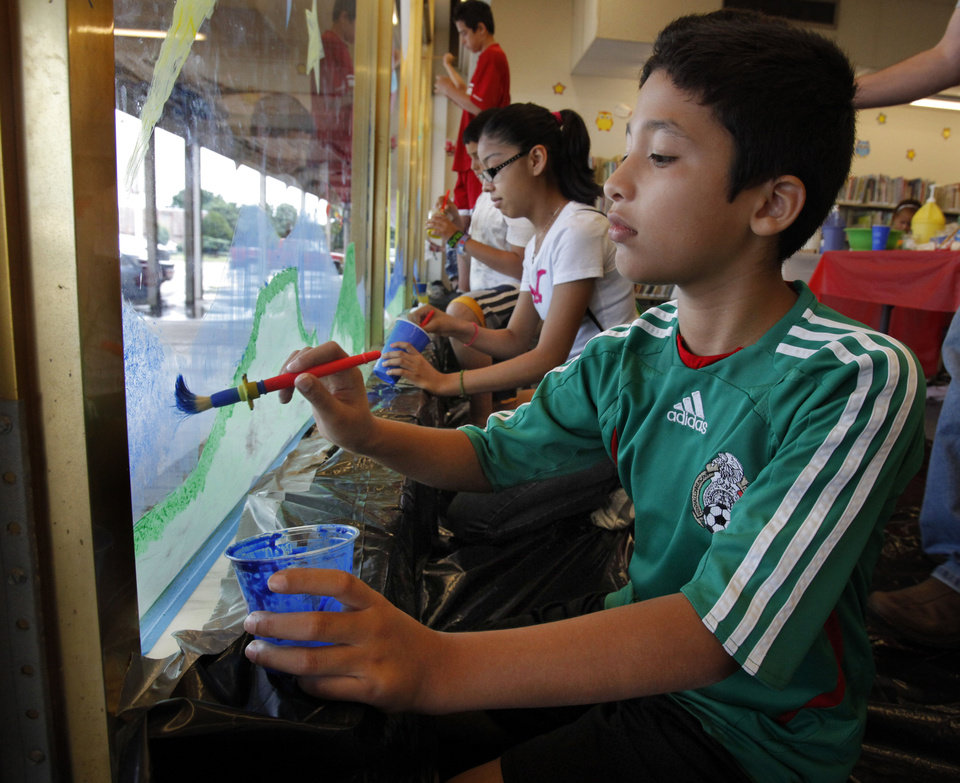 Photo - Daniel Nino, 11, paints a space scene on the window during the Summer Reading Program kickoff at Southern Oaks Library on Wednesday.  Photo by Steve Sisney, The Oklahoman  STEVE SISNEY - THE OKLAHOMAN