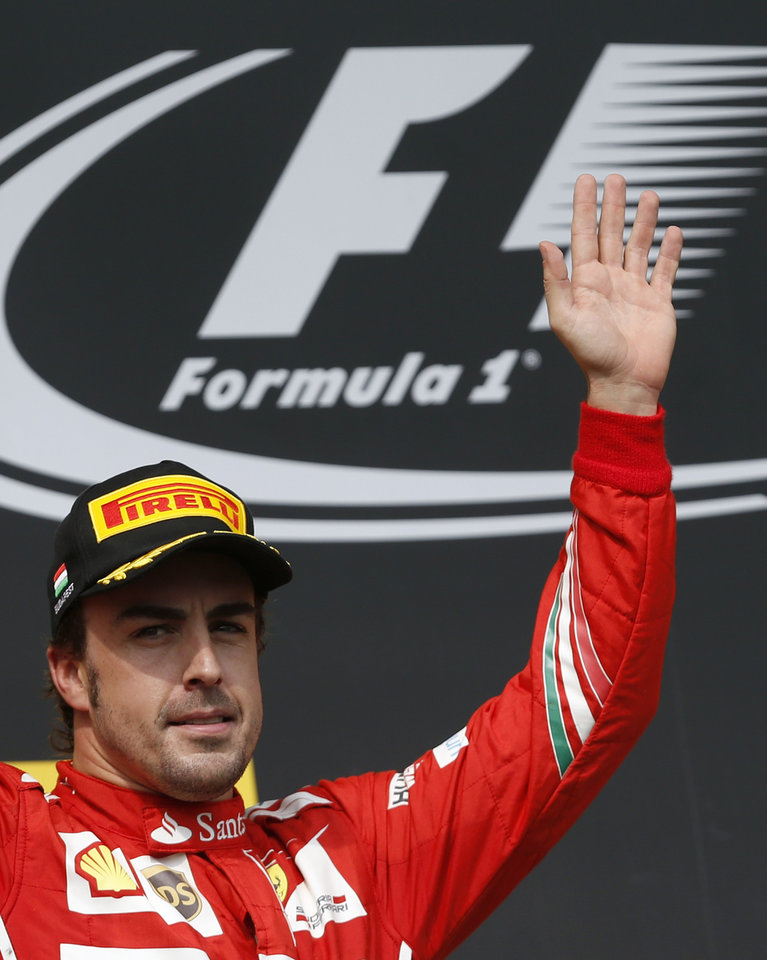 Photo - Ferrari driver Fernando Alonso of Spain greets spectators after placing second in the Hungarian Formula One Grand Prix in Budapest, Hungary, Sunday, July 27, 2014. Hamilton placed third in the race. (AP Photo/Darko Vojinovic)