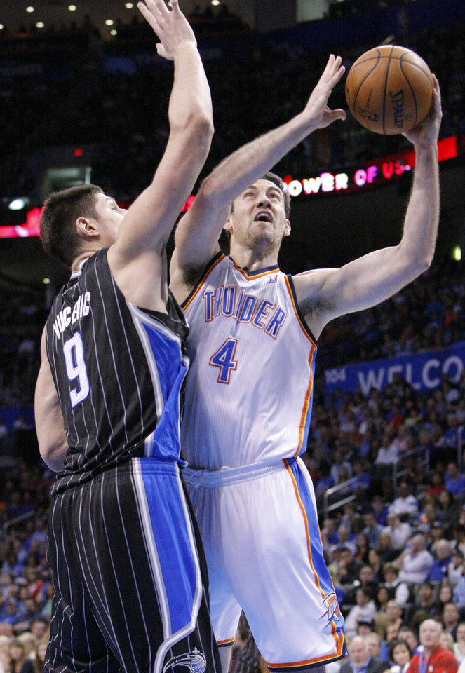 Photo - Orlando Magic center Nikola Vucevic (9) defends as Oklahoma City Thunder's Nick Collison (4) goes up for the basket during the fourth quarter of an NBA basketball game in Oklahoma City, Friday, March 15, 2013. Oklahoma City won 117-104.  (AP Photo/Alonzo Adams)