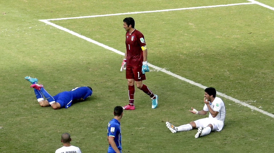 Photo - Italy's Giorgio Chiellini, left, lays on the pitch after Uruguay's Luis Suarez, right, ran into him with his teeth during the group D World Cup soccer match between Italy and Uruguay at the Arena das Dunas in Natal, Brazil, Tuesday, June 24, 2014. (AP Photo/Hassan Ammar)