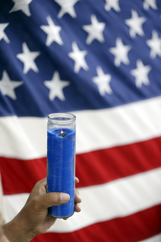 A demonstrator holds a candle in front of an American flag during an immigration demonstration, in Doral, Fla., Wednesday, May 1, 2013. Demonstrators demanded an overhaul of immigration laws Wednesday in an annual, nationwide ritual that carried a special sense of urgency as Congress considers sweeping legislation that would bring many of the estimated 11 million people living in the U.S. illegally out of the shadows. (AP Photo/Wilfredo Lee)