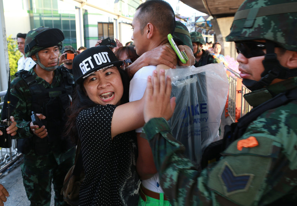 Photo - A woman protester, second left, tries to free her colleague who was detained by Thai soldiers at the Victory Monument during an anti-coup demonstration in Bangkok, Thailand Saturday, May 24, 2014. Thailand's coup leaders said Saturday that they would keep former Prime Minister Yingluck Shinawatra, Cabinet members and anti-government protest leaders detained for up to a week to give them