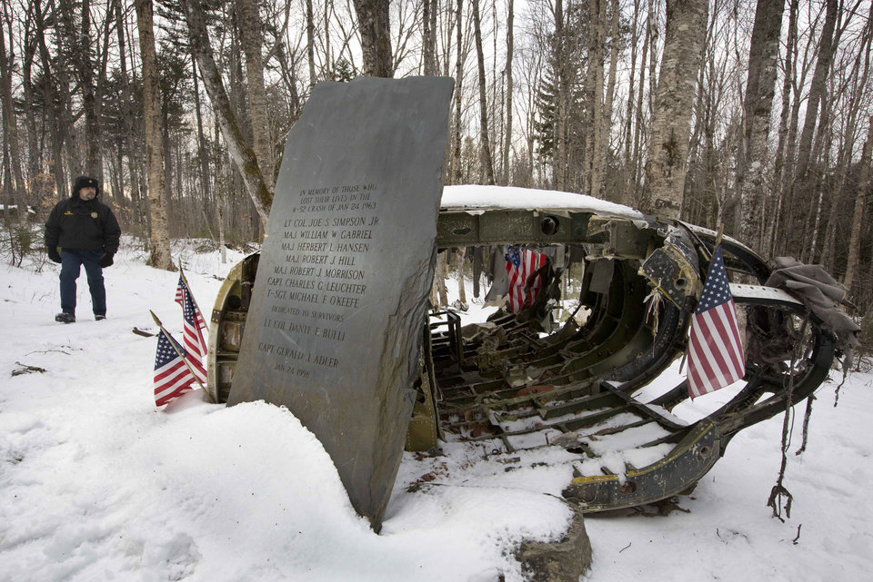 Photo - HOLD FOR STORY MOVING MAY 25 BY DAVID SHARP FILE - In this Dec. 14, 2012 file photo, Greenville, Maine, Police Chief Jeff Pomerleau views a monument next to wreckage from a B-52 bomber on Elephant Mountain near Greenville, Maine. The plane's 40-foot-tall vertical stabilizer had snapped off, and the plane crash in January 1963 killed seven of the nine people on board. Air Force personnel from around the country gathered in Greenville, Saturday, May 25, 2013 to remember the deadly crash. (AP Photo/Robert F. Bukaty, File)