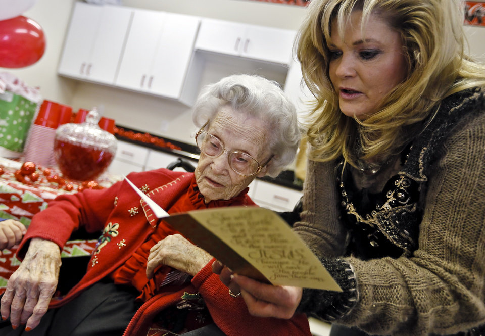 Photo - Leisa Davis reads a card to Ora E. Holland during her early birthday celebration at Heritage Assisted Living Center on Saturday, Dec. 22, 2012, in Oklahoma City, Okla. Holland will celebrate her 112th birthday on Dec. 24, 2012.   Photo by Chris Landsberger, The Oklahoman
