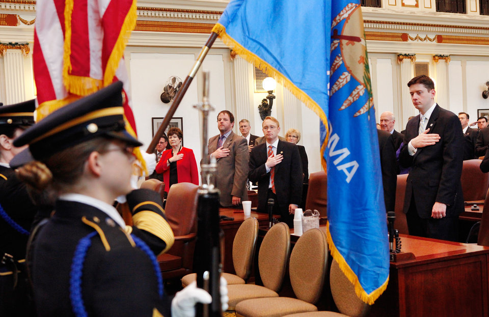Photo - Lawmakers honor the American flag, carried by a honor guard,  by standing and reciting the Pledge of Allegiance before Gov. Mary Fallin enters the chamber to deliver her 2012 State of the State address to a joint session of the Oklahoma legislature in the House Chamber on the opening day of the session, Monday, Feb, 6, 2012.   Photo by Jim Beckel, The Oklahoman