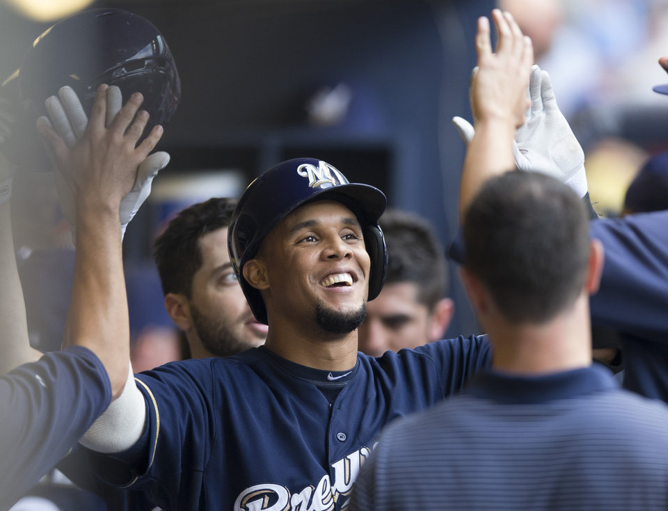 Carlos Gomez of the Milwaukee Brewers is greeted by teammates in the dugout after hitting a two run home run off of Jhoulys Chacin of the Colorado Rockies during the first inning of a baseball game Saturday, June 28, 2014, in Milwaukee. (AP Photo/Tom Lynn)