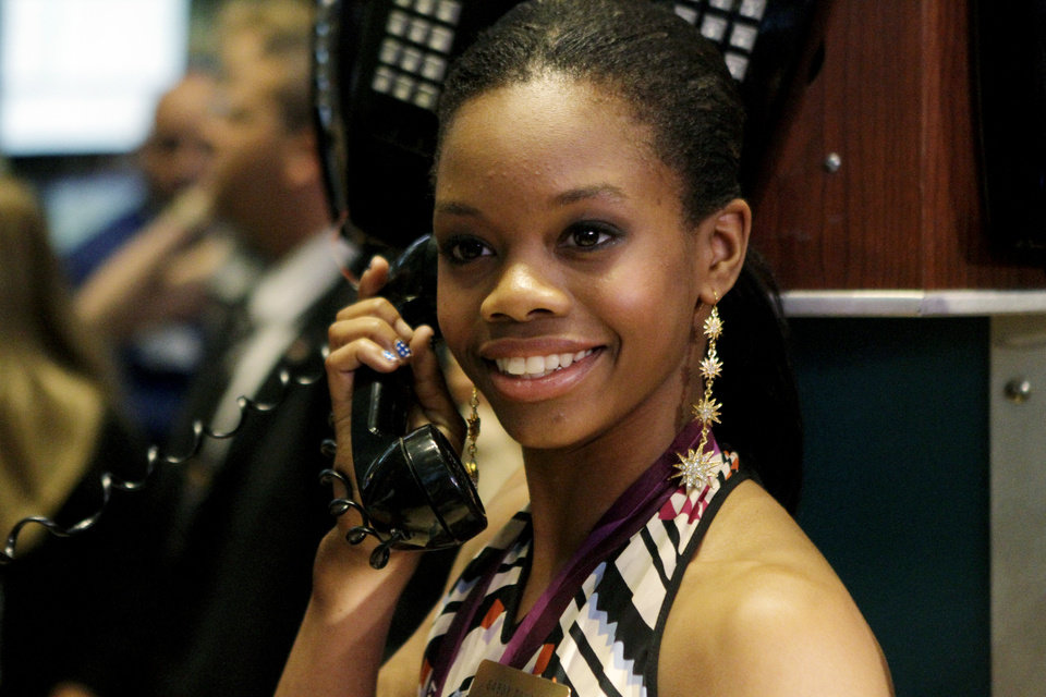 Photo -   Olympic champion gymnast Gabby Douglas pretends to talk on the phone while posing for photos on the floor of the New York Stock Exchange, Tuesday, Aug. 14, 2012, in New York. (AP Photo/Alex Katz)