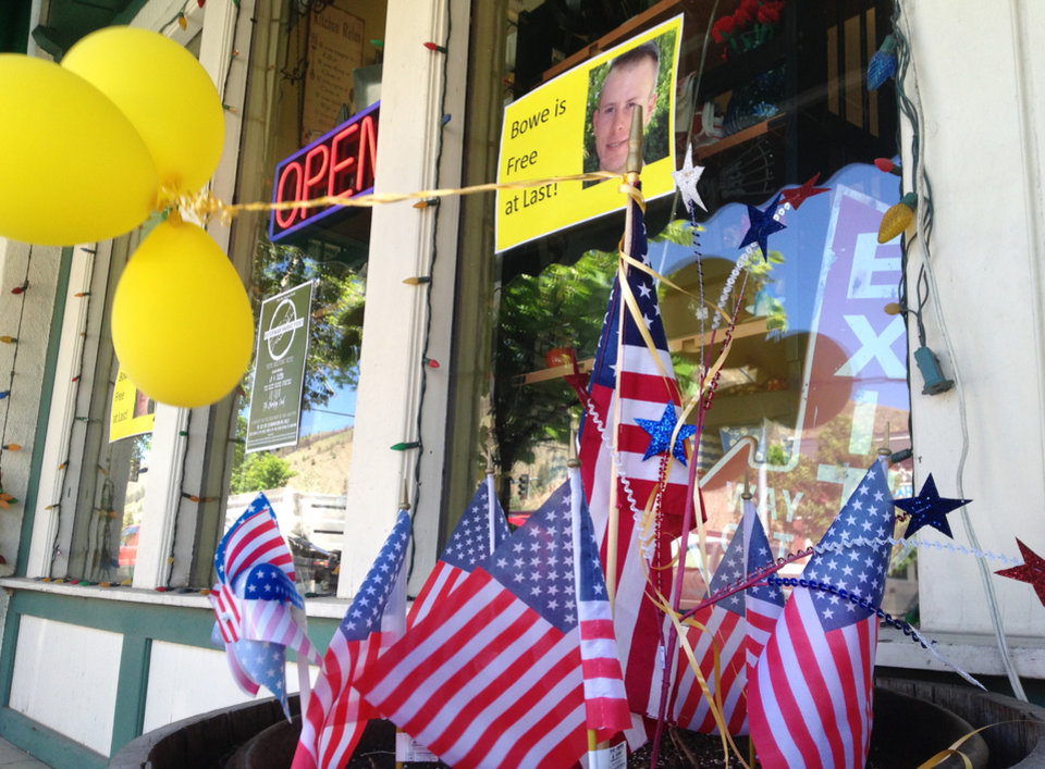 Photo - Flags and balloons marking the release from captivity of Sgt. Bowe Bergdahl adorn the sidewalk outside a shop in the soldier's hometown of Hailey, Idaho, Wednesday, June 4, 2014.  The exchange for five Taliban detainees from Guantanamo and the still-murky circumstances of how Bergdahl came to be captured nearly five years ago have prompted a fierce debate in Washington and across the country. (AP Photo/Brian Skoloff)