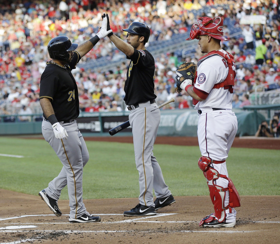 Photo - Pittsburgh Pirates' Pedro Alvarez (24) is greeted by Garreth Jones, center, after hitting a solo home run off Washington Nationals pitcher Stephen Strasburg during the second inning of a baseball game at Nationals Park, Wednesday, July 24, 2013, in Washington. At right is Nationals catcher Wilson Ramos. (AP Photo/Pablo Martinez Monsivais)