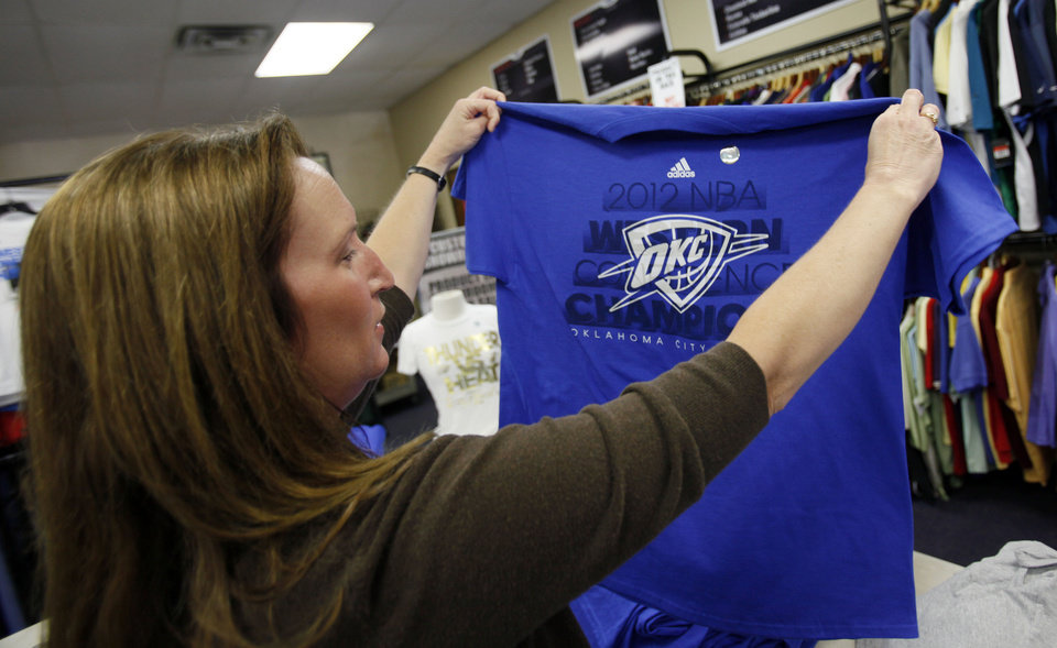 Photo - Tammy Lemmings holds up an Oklahoma City Thunder shirt that is still warm from the being printed at the USA Screen Printing and Embroidery's House of Bedlam shop, 3100 S. Meridian, in Oklahoma City, Wednesday, June 13, 2012. Photo by Nate Billings, The Oklahoman
