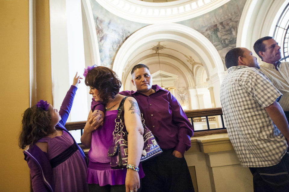 Photo - Alexis Gallegos, 9, points out details of the Pueblo County Courthouse's dome to her mothers Jamie and Bea as they wait in line with Randy Romero and Michael Ross for their marriage licenses in Pueblo, Colo., Friday, July 11, 2014. Technically, their state still does not recognize gay marriages. But that hasn't stopped hundreds of gay Coloradans from getting marriage licenses from two county clerks who argue they still have the legal right to provide them to loving couples. (AP Photo/The Colorado Springs Gazette, Julia Moss)