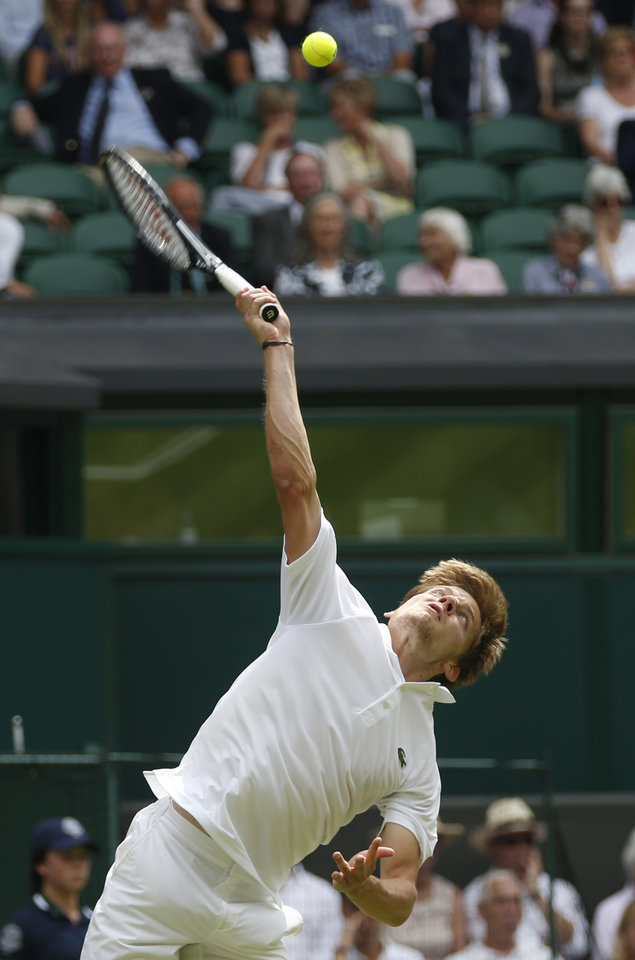 Photo - David Goffin of Belgium serves to Andy Murray of Britain during their first round match at the All England Lawn Tennis Championships in Wimbledon, London,  Monday, June  23, 2014. (AP Photo/Pavel Golovkin)