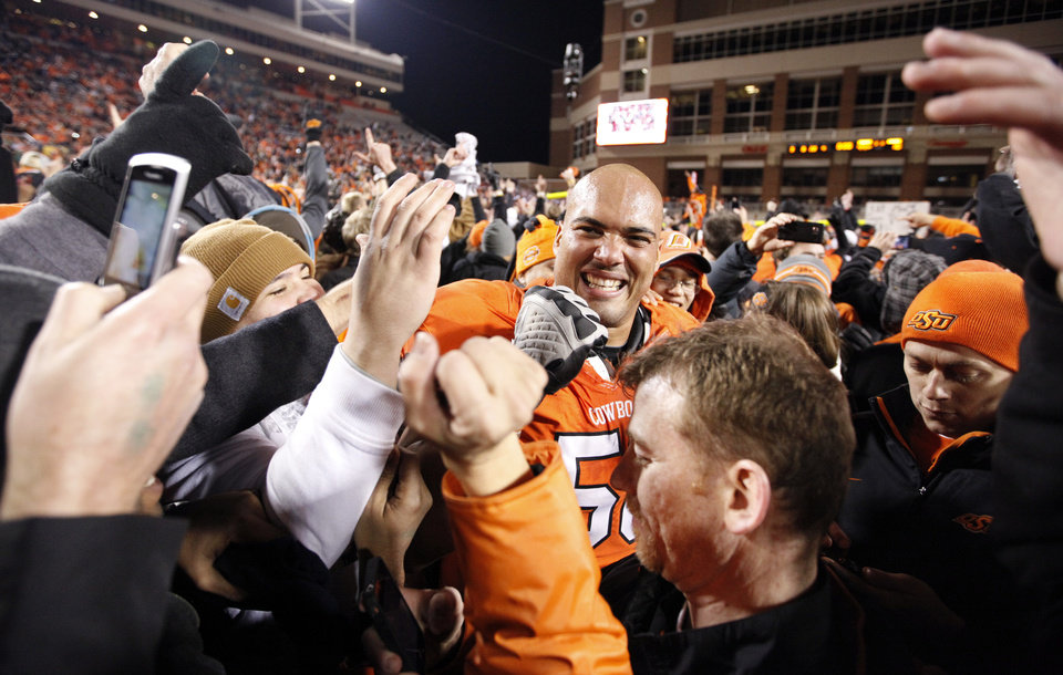 Photo - Oklahoma State's Jamie Blatnick (50) celebrates with fans during the Bedlam college football game between the Oklahoma State University Cowboys (OSU) and the University of Oklahoma Sooners (OU) at Boone Pickens Stadium in Stillwater, Okla., Saturday, Dec. 3, 2011. Photo by Sarah Phipps, The Oklahoman