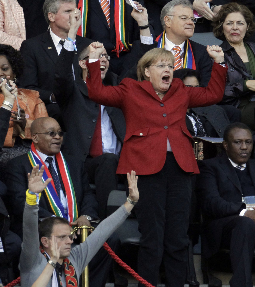 Photo - FILE - In this July 3, 2010 file photo German Chancellor Angela Merkel celebrates next to South African President Jacob Zuma, left, after Germany's Thomas Mueller scored a goal during the World Cup quarterfinal soccer match between Argentina and Germany at the Green Point stadium in Cape Town, South Africa. Merkel will travel to the World Cup final in Brazil _ giving Germany's most prominent fan perhaps her best chance yet to watch the team lift a trophy after eight years of steadfast support. President Joachim Gauck's office said Wednesday, July 9, 2014 that Gauck and Merkel will travel to Rio de Janeiro for the final against Argentina or the Netherlands.  (AP Photo/Gero Breloer, File)