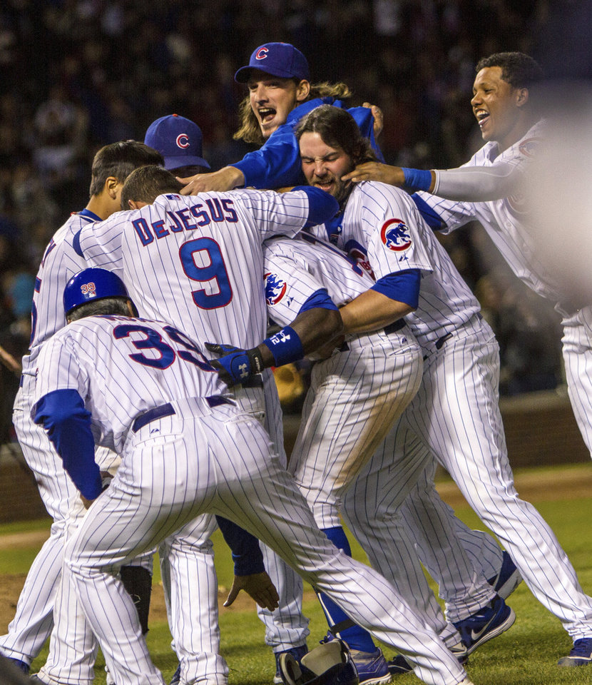 Photo -   Chicago Cub players jump onto Alfonso Soriano after Soriano drove in the winning run in the 10th inning, giving the Cubs a 3-2 win over the St. Louis Cardinals in a baseball game in Chicago on Tuesday, April 24, 2012. (AP Photo/Charles Cherney)