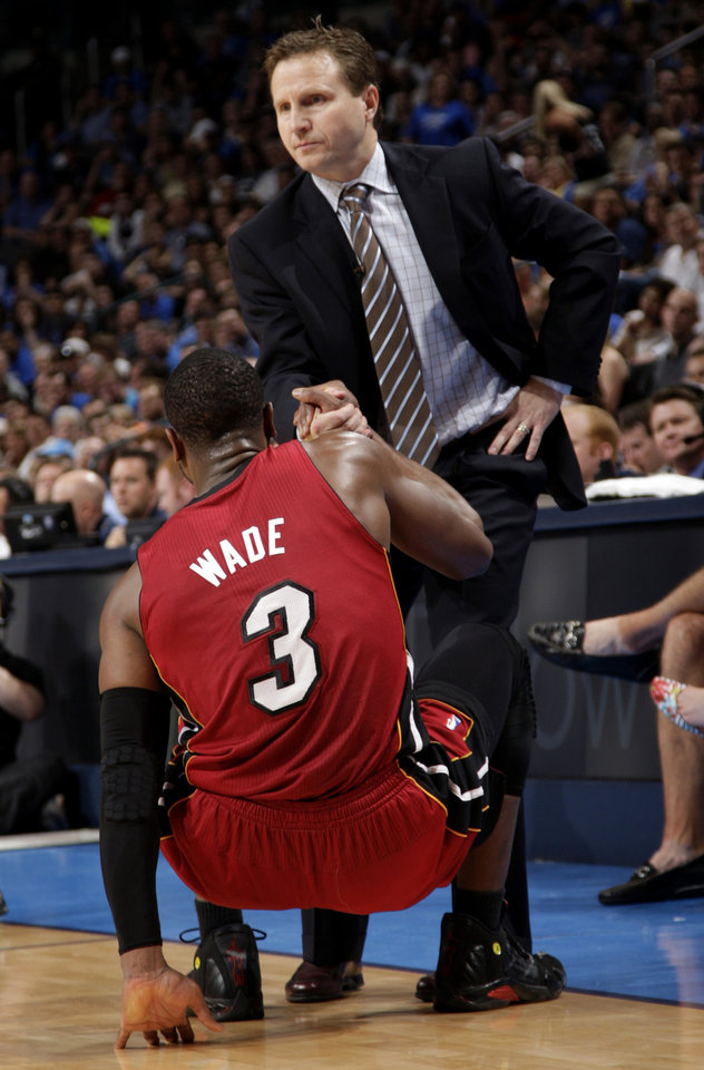 Photo - Oklahoma City head coach Scott Brooks helps up Miami's Dwyane Wade (3) during the NBA basketball game between the Miami Heat and the Oklahoma City Thunder at Chesapeake Energy Arena in Oklahoma City, Sunday, March 25, 2012. Photo by Sarah Phipps The Oklahoman