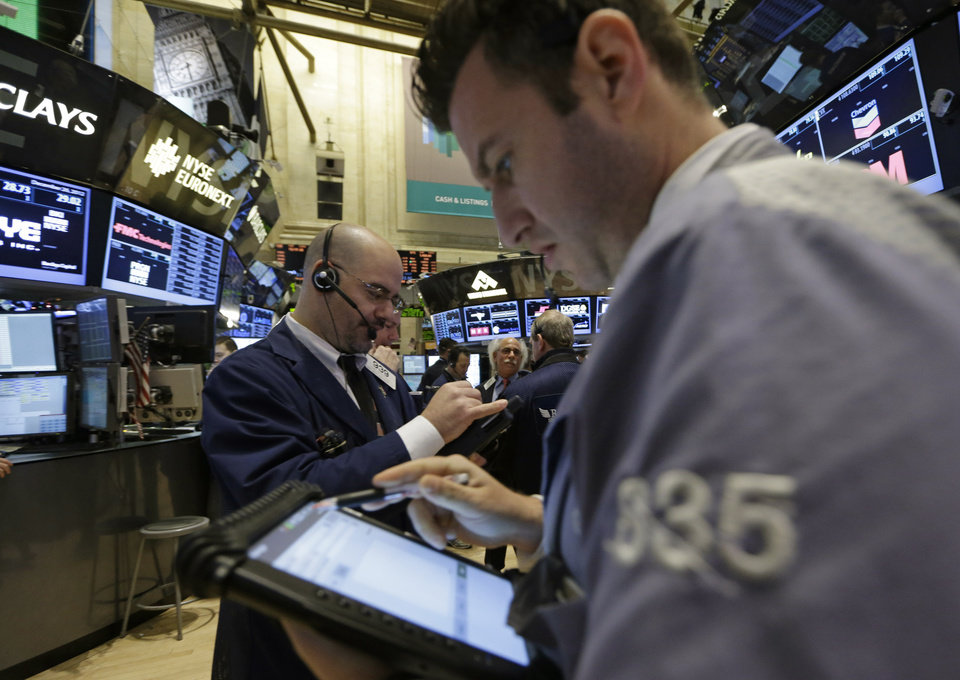 Photo - Floor traders check their handheld computers at the New York Stock Exchange in New York, Wednesday, Dec. 26, 2012.  (AP Photo/Kathy Willens)