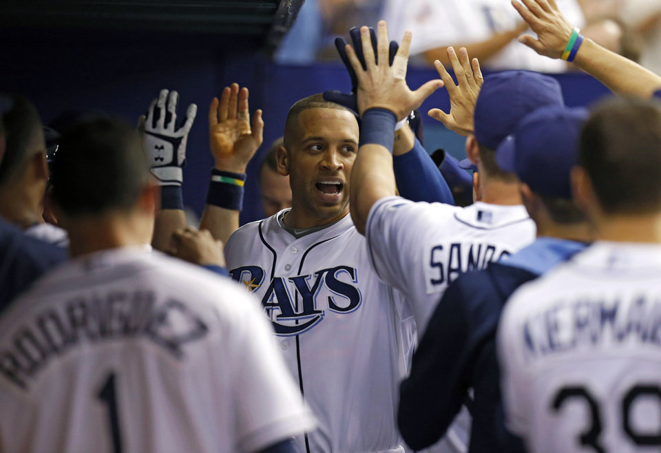 Photo - Tampa Bay Rays' James Loney is congratulated after scoring during the fourth inning of a baseball game against the St. Louis Cardinals Wednesday, June 11, 2014, in St. Petersburg, Fla. (AP Photo/Mike Carlson)