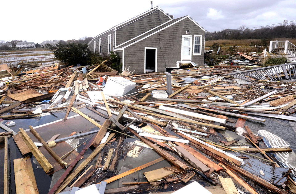 Photo - Debris floats around a house pushed off it's foundation in the aftermath of superstorm Sandy in East Haven, Conn., Tuesday, Oct. 30, 2012.  Sandy, the storm that made landfall Monday, caused multiple fatalities, halted mass transit and cut power to more than 6 million homes and businesses. (AP Photo/Jessica Hill) ORG XMIT: CTJH111