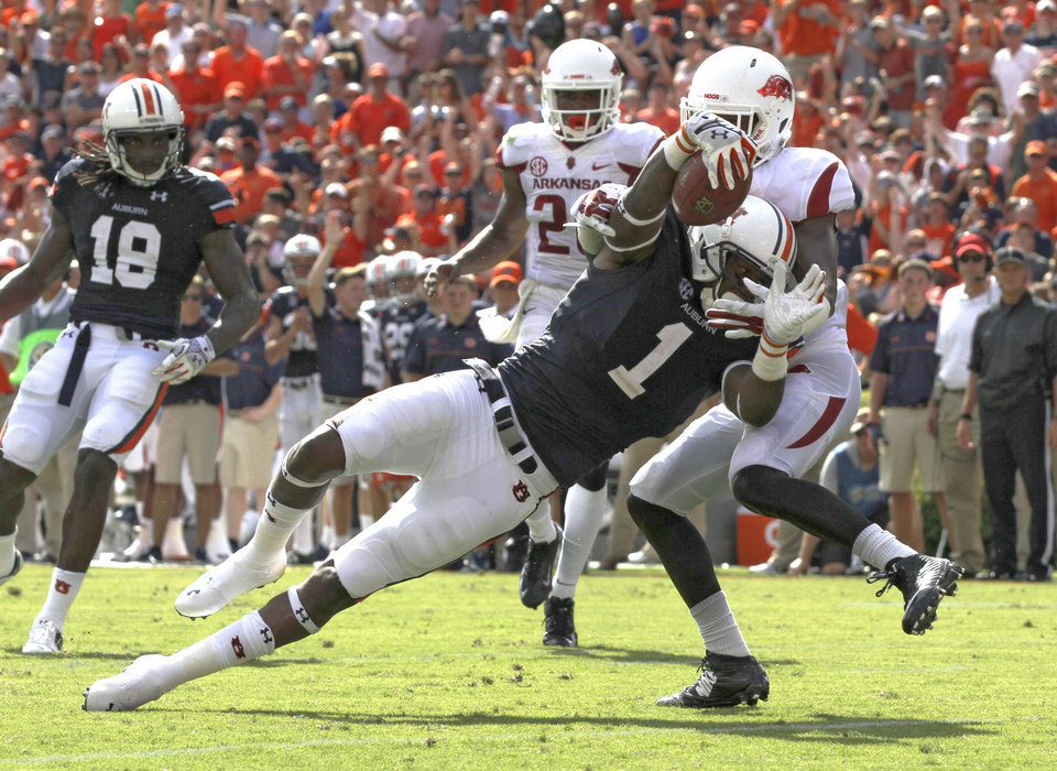 Photo - Auburn wide receiver D'haquille Williams (1) dives for the end zone for a touchdown as Arkansas cornerback Carroll Washington (21) tries to tackle him during the first half of an NCAA college football game on Saturday, Aug. 30, 2014, in Auburn, Ala. (AP Photo/Butch Dill)