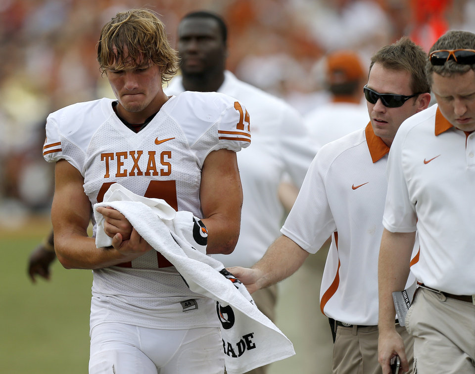 Photo - UT's David Ash (14) walks off the field after an injury during the Red River Rivalry college football game between the University of Oklahoma (OU) and the University of Texas (UT) at the Cotton Bowl in Dallas, Saturday, Oct. 13, 2012. Oklahoma won 63-21. Photo by Bryan Terry, The Oklahoman