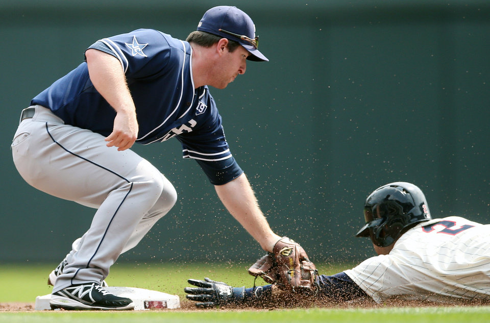 Photo - San Diego Padres second baseman Jedd Gyorko, left, reaches to tag Minnesota Twins' Brian Dozier who was called safe as he stole second base in the first inning of a baseball game, Wednesday, Aug. 6, 2014, in Minneapolis. (AP Photo/Jim Mone)