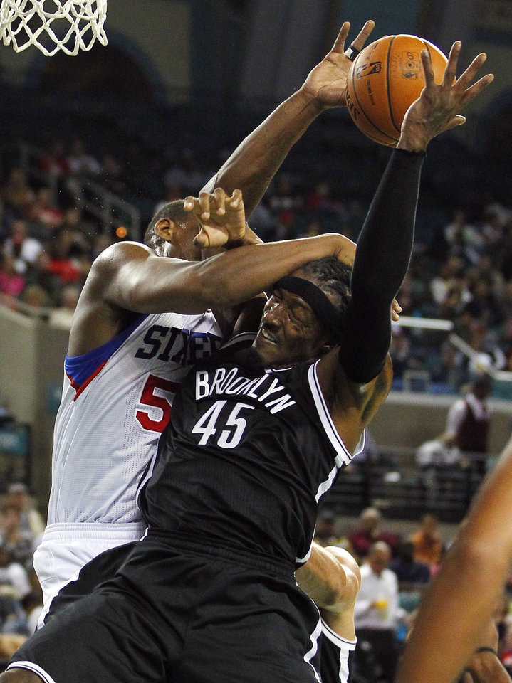 Photo -   Brooklyn Nets' Gerald Wallace (45) is fouled by Philadelphia 76ers' Kwame Brown during an NBA preseason basketball game in Atlantic City , N.J., Saturday, Oct. 13, 2012. The Nets defeated the 76ers 108-105 in overtime. (AP Photo/Rich Schultz)