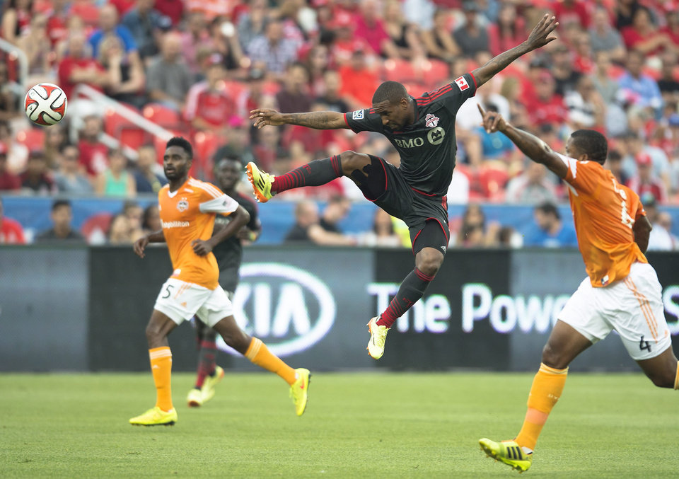 Photo - Toronto FC's Jermain Defoe, center, leaps for a ball during the first half of a soccer game against the Houston Dynamos in Toronto on Saturday, July 12, 2014. (AP Photo/The Canadian Press, Darren Calabrese)